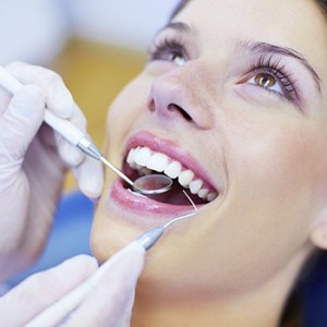Closeup of a happy woman with a bright, white smile getting her teeth checked